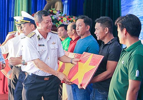 Chuẩn đô đốc Đặng Minh Hải trao tặng cờ Tổ quốc cho ngư dân miền Trung. Ảnh: N.Đ.