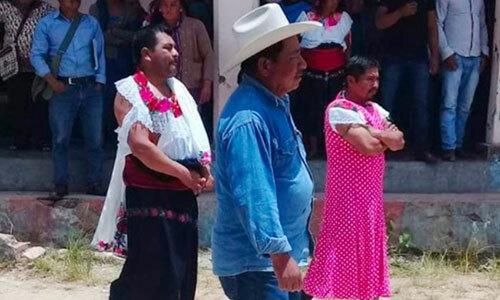 Javier Jimenez, áo trắng, và Luis Ton, váy hồng bị bắt đi diễu hành trong trang phục phụ nữ. Ảnh: Twitter.