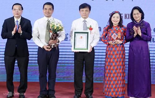 Phó chủ tịch nước Đặng Thị Ngọc Thịnh (áo dài tím) và Bộ trưởng Chu Ngọc Anh (bìa trái) trao giải nhất năm 2018cho giải pháp cải tiến dàn quạt tạo oxy để tiết kiệm điện trong nuôi tôm. Ảnh: MH.
