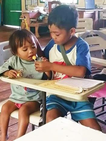 Agusan bóc kẹo cho em ăn để dỗ em ngồi ngoan. Ảnh: Herald Hope Tero-Mangle Apole