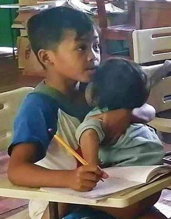 Agusan vừa bế em ngủ vừa nghe giảng và viết bài. Ảnh: Herald Hope Tero-Mangle Apole