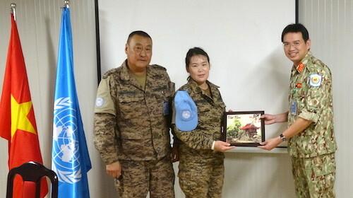 Trung tá Bùi Đức Thành, Giám đốc bệnh viện dã chiến (phải) tặng quà lưu niệm cho bệnh nhân thứ 1.000 của đơn vị. Ảnh: BVDC