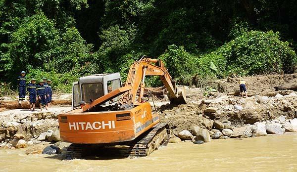 Máy xúc đào xới các vị trí nghi có người bị vùi lấp dọc suối Son. Ảnh: Lê Hoàng.