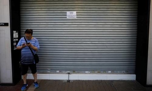 Một người qua đường đứng trước cửa tiệm dán thông báo đóng cửa vì biểu tình ở Hong Kong hôm 5/8. Ảnh: Reuters.