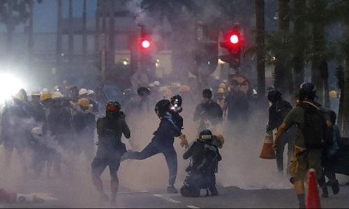 Người biểu tình trên đường phố Hong Kong ném lại ống đựng đạn hơi cay được bắn bởi cảnh sát chống bạo động ngày 12/8.Ảnh: AP.