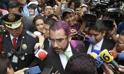 Người đứng đầu cơ quan an ninh công cộng Mexico City Jesus Orta, cà vạt xanh, bị đám đông người biểu tình vây quanh ngày 12/8. Ảnh: AFP.