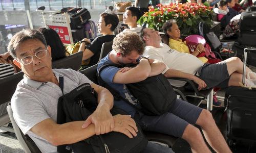 Hành khách ngồi chờ tại sân bay Hong Kong sáng 13/8. Ảnh: SCMP.