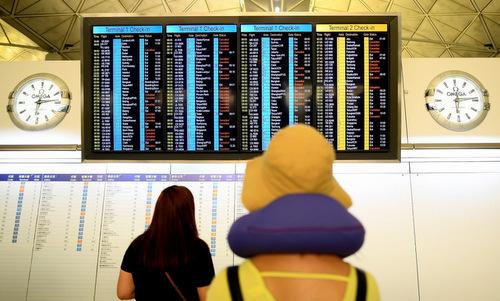 Hành khách theo dõi danh sách chuyến bay bị hủy tại sân bay Hong Kong sáng 13/8. Ảnh: SCMP.
