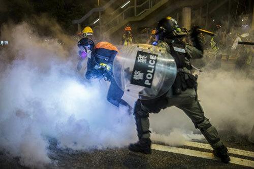 Cảnh sát phun hơi cay đối phó với người biểu tình ở quận Causeway Bay, Hong Kong hôm 4/8. Ảnh: AFP
