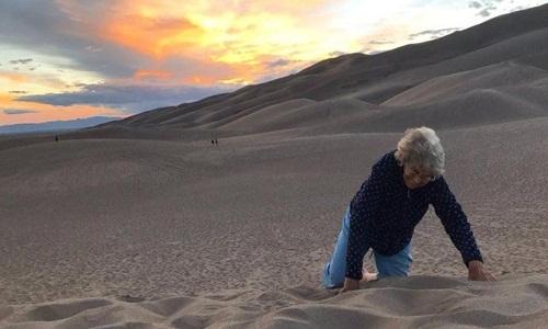 Bà Joy trải nghiệm lăn xuống đồi cát. Ảnh: Facebook.