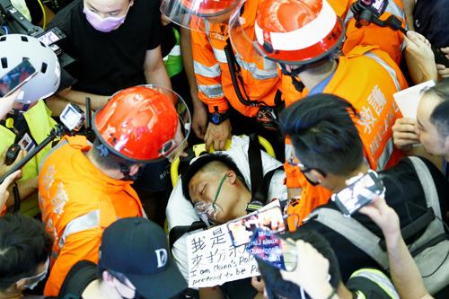 Nam thanh niên được đưa đi cấp cứu sau khi bị người biểu tình tấn công ở sân bay Hong Kong tối 13/8, bên cạnh là tấm bảngtôi là cảnh sát Trung Quốc đóng giả làm hành khách do người biểu tình viết. Ảnh: Reuters.