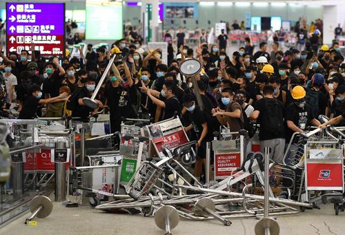Người biểu tình chặn lối vào sảnh sân bay quốc tế Hong Kong hôm 13/8. Ảnh: AFP.