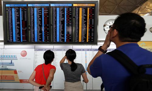 Hành khách theo dõi chuyến bay tại Hong Kong hôm 13/8. Ảnh: Reuters.