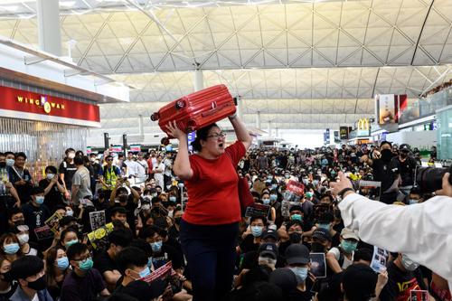 Nữ hành khách chật vật tìm lối thoát khi người biểu tình tràn vào sân bay quốc tế Hong Kong hôm 13/8. Ảnh: AFP.