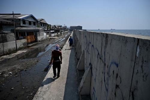 Người dân địa phương đi sát bức tường chắn biển khổng lồ, tránh chỗ đường ngập nước bên cạnh dãy nhà kho bỏ hoang ở phía bắc Jakarta hôm 12/6. Ảnh: AFP.