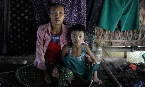 Hle Hle Saw, nạn nhân của bạo hành gia đình, cùng con trai tại ngôi làng ở vùng Ayeyarwady, Myanmar, ngày 7/8. Ảnh: Reuters.