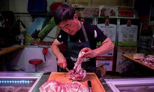 Chủquầy hàng thịt lợn trong một khu chợ ở Bắc Kinh. Ảnh: AFP.