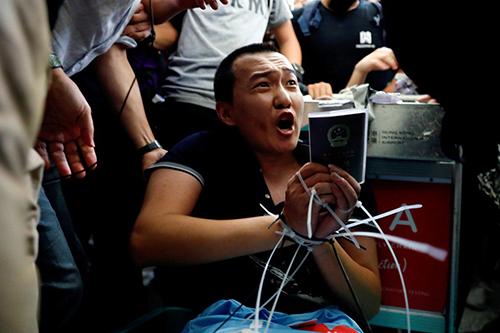 Phóng viên Phó Quốc Hào bị người biểu tình Hong Kong trói tay ở sân bay ngày 13/8. Ảnh: SCMP.