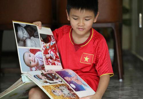 Bé Lường Quốc Bảo,con trai duy nhất của liệt sĩ Lường PhátChiêm lật giở những trang ký ức của gia đình. Lúc ba hy sinh, Bảo 18 tháng tuổi. Ảnh: Ngọc Thành.
