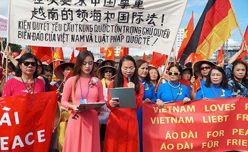 Đại diện hội người Việt tại Đức đọc bức thư phản đối các hành vi xâm phạm chủ quyền Việt Nam trước sứ quán Trung Quốc ở Berlin. Ảnh: Huy Thắng