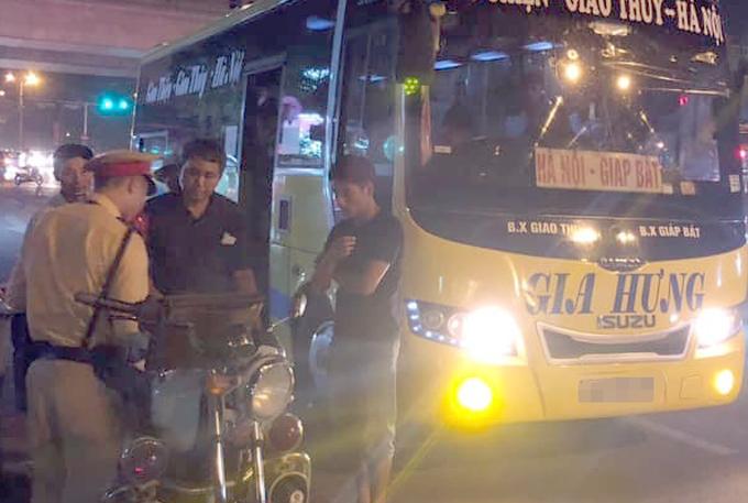 Tổ công tác CSGT đã dừng xe và lập biên bản xử phạt tài xế xe khách chở quá số người quy định. Ảnh. Xuân Phương