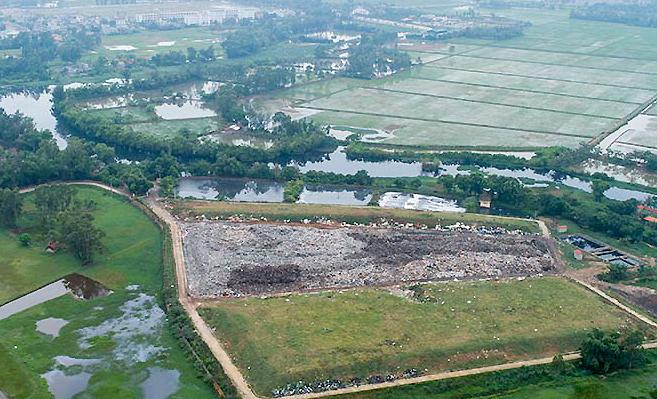 Bãi rác Sầm Sơn nằm sát dòng sông Đơ khiến nước thải rò rỉ ra sông đen ngòm. Ảnh: Lê Hoàng.