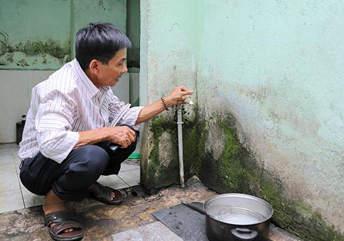 Ông Đặng Em chờ cả buổi sáng vẫn không hứng được nước thuỷ cục. Ảnh: Nguyễn Đông.
