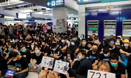 Người biểu tình ngồi trong nhà ga Yuen Long, tây bắc Hong Kong tối 21/8. Ảnh: AP.
