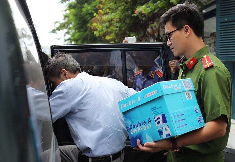 Cảnh sát thu giữ tài liệu tại nhà nghi can ở quận 1. Ảnh: Thành Nguyễn.