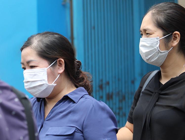 Nguyễn Thị Nguyên (trái) bị đưa khỏi Công ty TNHH TMDV Lữ hành Hòa Bình Quốc tế, sáng nay. Ảnh: Thành Nguyễn.