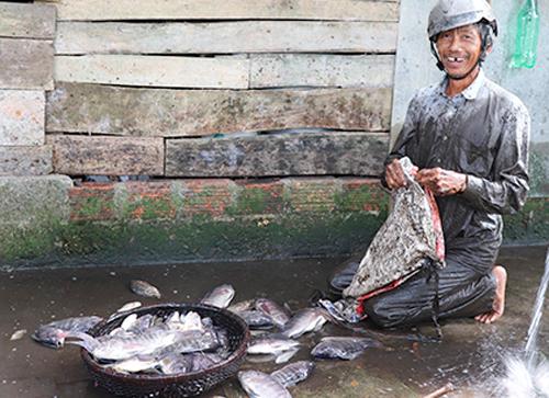 Ông Huỳnh nói sẽ mang cá cho người thân để cùng chia vui trong ngày hội. Ảnh: Hoàng Táo