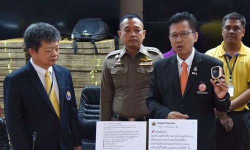 Đại diện Cơ quan Phòng chống Tội phạm và Bảo vệ Người tiêu dùng Thái Lan cầm trên tay thiết bị tiết kiệm điện giả mạo được quảng cáo trên trang Facebook Expert Electric. Ảnh: Bangkok Post.
