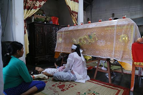 Con gái đầu bốn tuổi ngủ bên quan tài người cha. Ảnh:Hoàng Táo