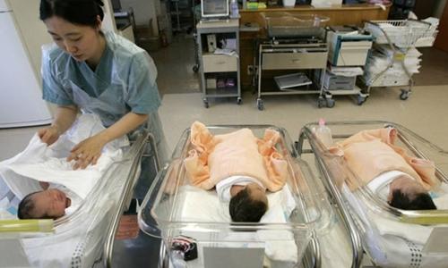 Y tá chăm sóc trẻ sơ sinh trong một bệnh viện ở Hàn Quốc. Ảnh: Reuters.