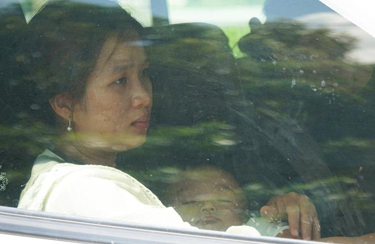 Một nữ hành kháchbế con mệt mỏi chờ xe qua cầu Rạch Miễu. Ảnh: Hoàng Nam.