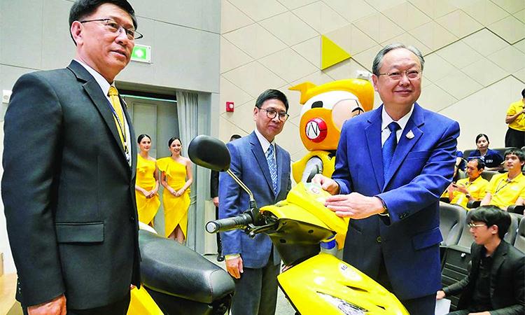 Ông Sontirat Sontijirawong (áo xanh bên phải), Bộ trưởng Năng lượng gắn nhãn dán cho một chiếc xe máy điện Toyotron Motor do Thái Lan sản xuất, một trong 12 nhà sản xuất xe máy điện địa phương.