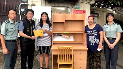 Nữ sinh Huang(áo kẻ ngang) được giới chứctặng bàn học hôm 1/9. Ảnh: CNA