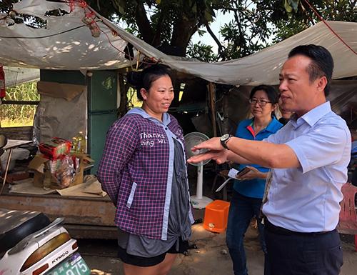 Bà Nguyễn nói chuyện với các quan chức huyện Gia Nghĩa tại căn lều tạm bợ sống cùng hai con hôm 1/9. Ảnh: CNA
