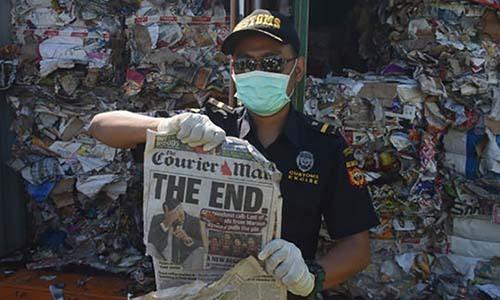 Nhân viên hải quan Indonesia giơ một tờ báo trong container rác thải tại Surabaya hôm 9/7. Ảnh: AP.