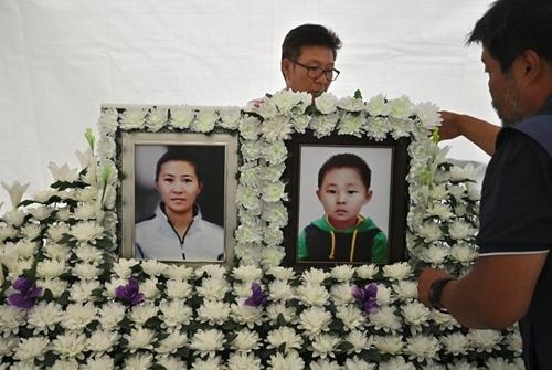 Một người đàn ông dựng chân dung của Han Sung-ok và con trai trong căn trướng tạm thời làm nơi tổ chức tang lễ ở Seoul hôm 29/8. Ảnh: AFP.