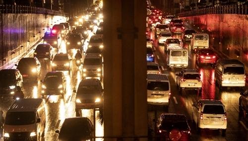 Một xe cứu thương (trái) đang xin đường giữa giờ cao điểm dọc đường cao tốc EDSA ở Manila hôm 5/8. Ảnh: AFP.