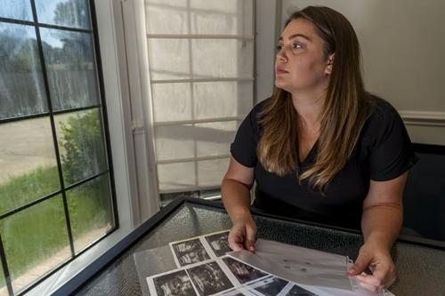 Heven Lunsford cầm ảnh siêu âm và giấy in dấu chân, dấu tay con trai chưa chào đời tại nhà riêng ở Alabama hôm 29/8. Ảnh: AP.