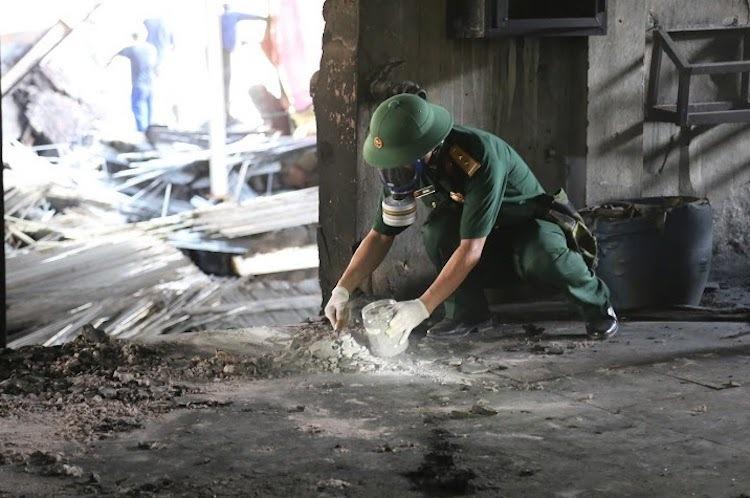 Cán bộ Viện Hoá học Môi trường Quân sự (Binh chủng Hoá học) lấy mẫu vật chất quanh nhà kho Rạng Đông chiều 5/9. Ảnh: Hoàng Thùy.