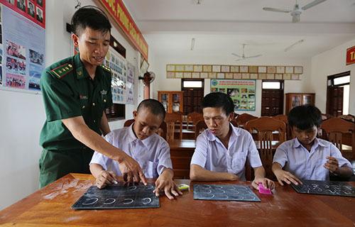 Thượng úy Lê Văn Chính bày cho hoc sinh viết chữ. Ảnh: Đắc Thành.