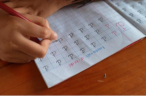 Một em học sinh có đôi tay bị tật nguyền nên viết chữ gặp khó khăn. Ảnh: Đắc Thành.