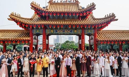 Các cặp vợ chồng chụp ảnh kỷ niệm tại đền Thiên Hậukhi kết thúc lễ cưới hôm nay. Ảnh: Reuters.