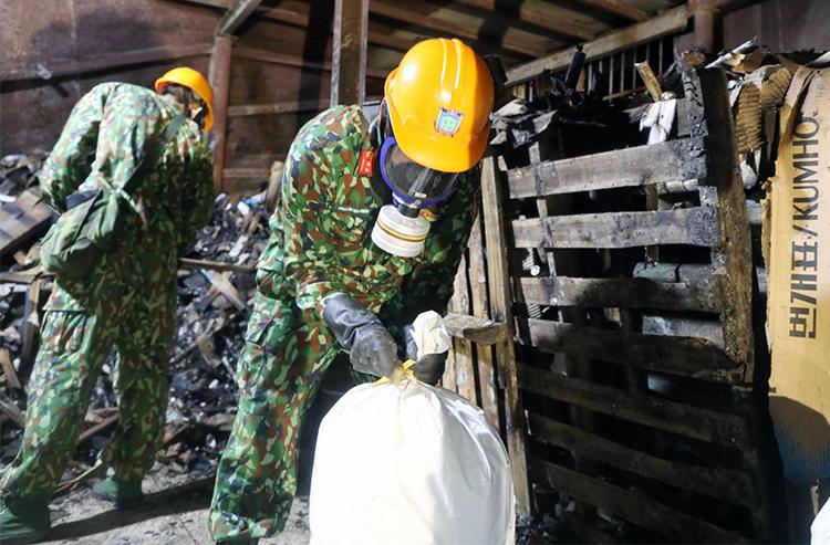 Bộ đội Hóa học đang tiến hành thu gom chất thải và tẩy độc. Ảnh: Ngọc Thành.