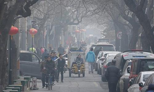 Người dân đi lại trên một con phố ở trung tâm Bắc Kinh ngày 2/3. Ảnh: Reuters.