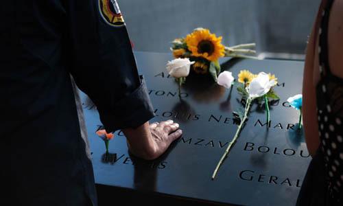 人们在9/11的纽约9/11国家纪念碑上放花。 照片:法新社。
