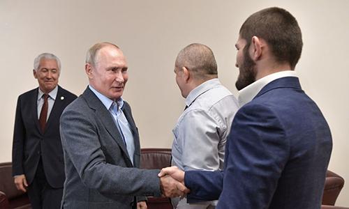 Tổng thống Vladimir Putin (phía trước, bên trái) bắt tay với võ sĩ Khabib Nurmagomedo (phía trước, bên phải) tại sân bay Makhachkala, Dagestan, Nga ngày 12/9. Ảnh: Điện Kremlin.